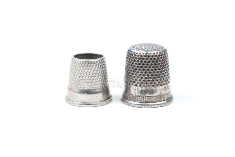 Two metal silver sewing thimbles on a white background. Sewing accessories and tools. royalty free stock image
