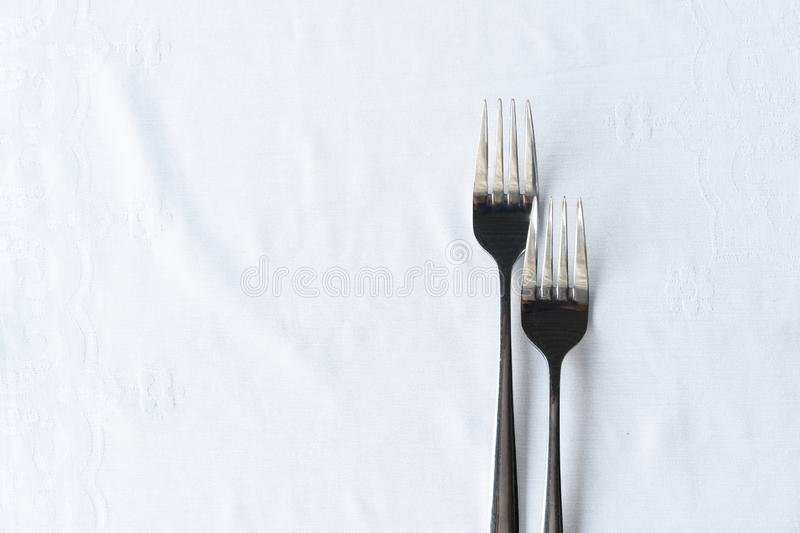 Two of metal stainless steel fork on white tablecloth for food dinner background royalty free stock image