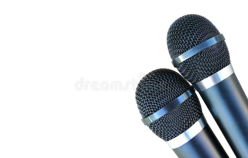 Two microphones for karaoke - black, wireless, metal. isolated on white background. left space for text. Two microphones for karaoke - black, wireless, metal royalty free stock images