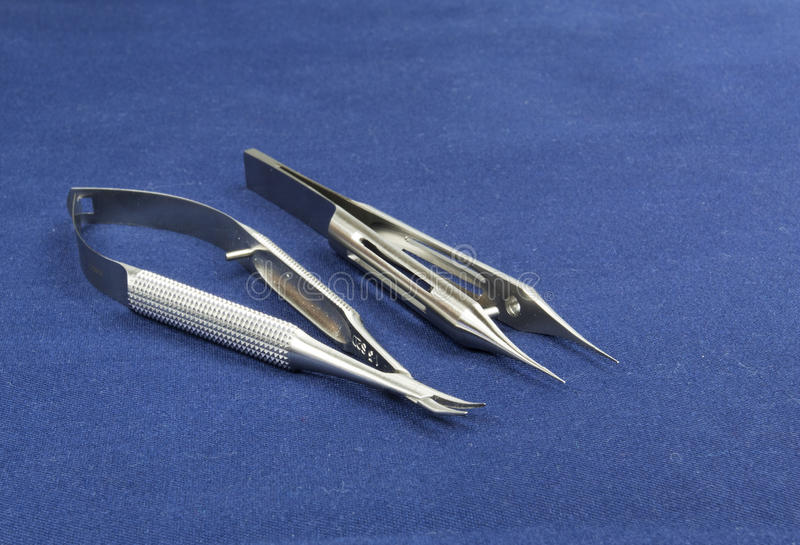 Two microsurgical instruments on blue background stock photography