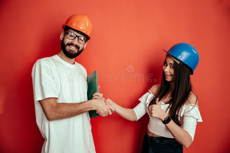 Two mid adults constructors workers giving hand shake isolated on red background stock images