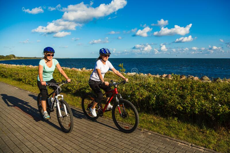 Two active women in sportswear riding bicycles at seashore in summer royalty free stock images