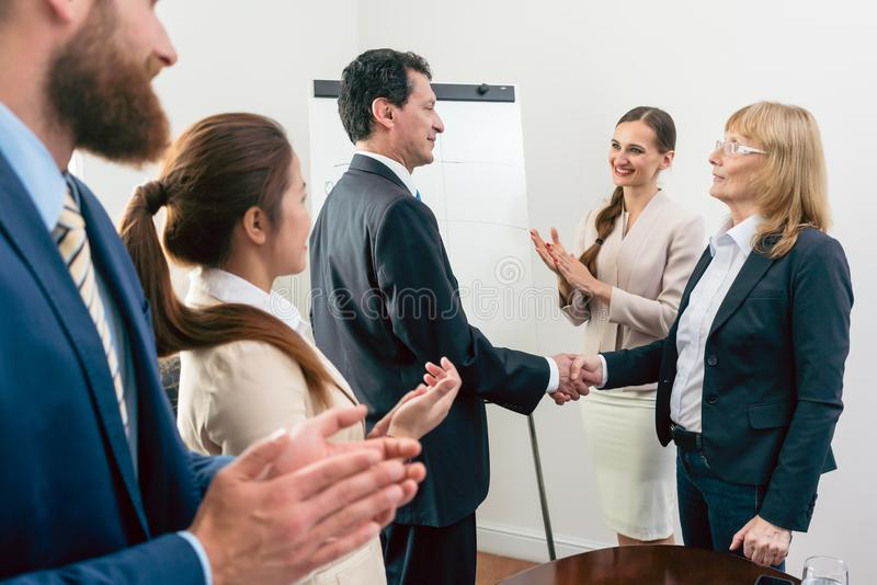 Two middle-aged business associates smiling while shaking hands. As agreement after meeting in the conference room of a multinational company stock photography