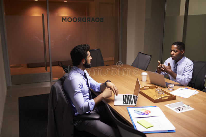 Two middle aged businessman working late in an office royalty free stock photography