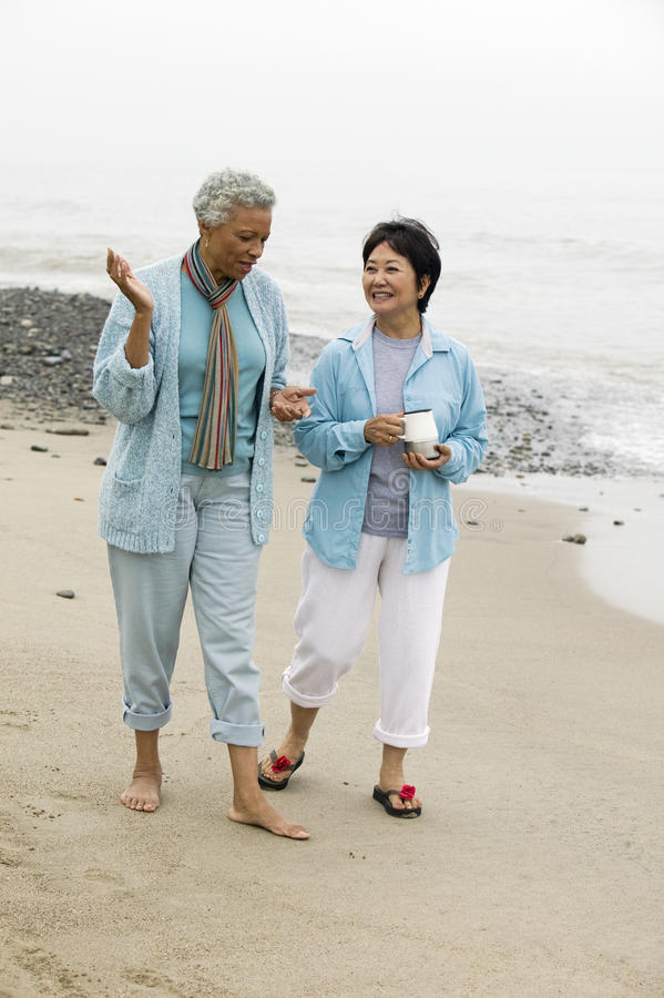 Two middle-aged women talking on beach stock image