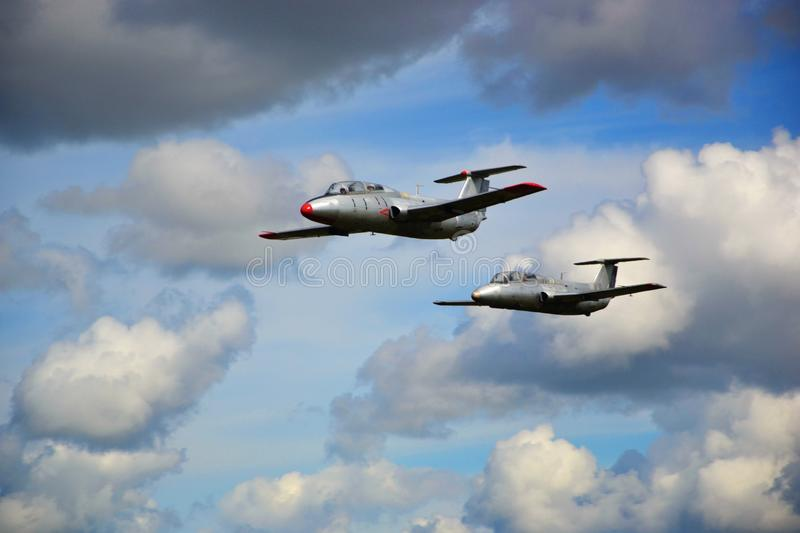 Two military aircraft flying in white clouds royalty free stock photo