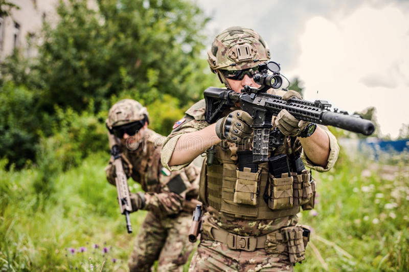 Two military man snipers with airsoft automatic rifle. Two military men snipers with airsoft automatic rifle with a telescopic sight lies in grass in forest royalty free stock images