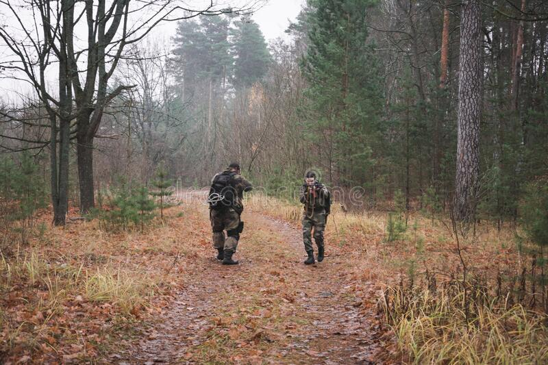 Two military men with machine guns and camouflage in the forest. Military concept stock photo