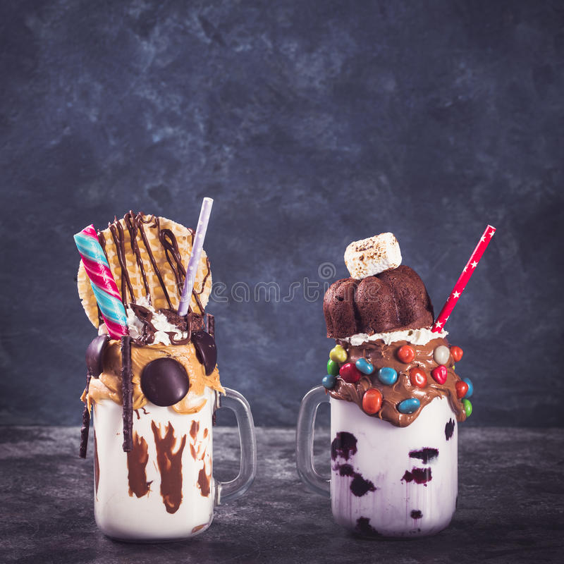 Two milkshakes with copy space. Two homemade extreme milkshakes jars with copy space. Toned royalty free stock photo