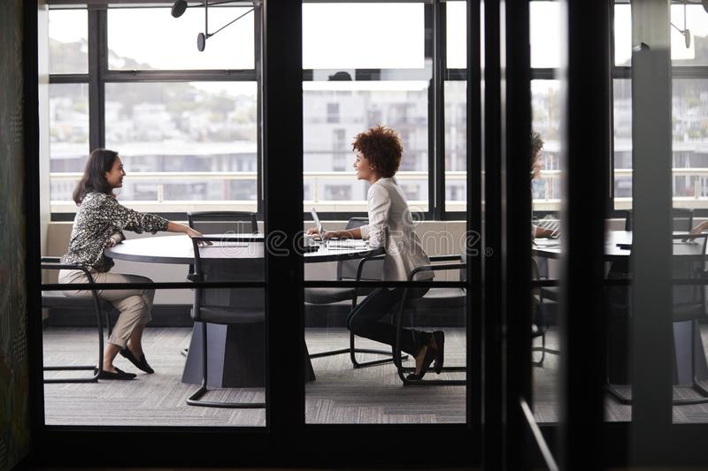 Two millennial businesswomen meeting for a job interview, full length, seen through glass wall royalty free stock photo