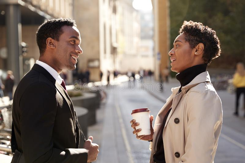 Two millennial coworkers standing on a sunny street in the city talking, waist up royalty free stock image