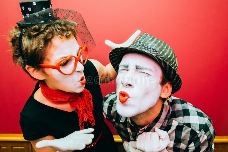 Two mimes posing against a red wall background. Two mimes showing emotions on the wall background royalty free stock photo