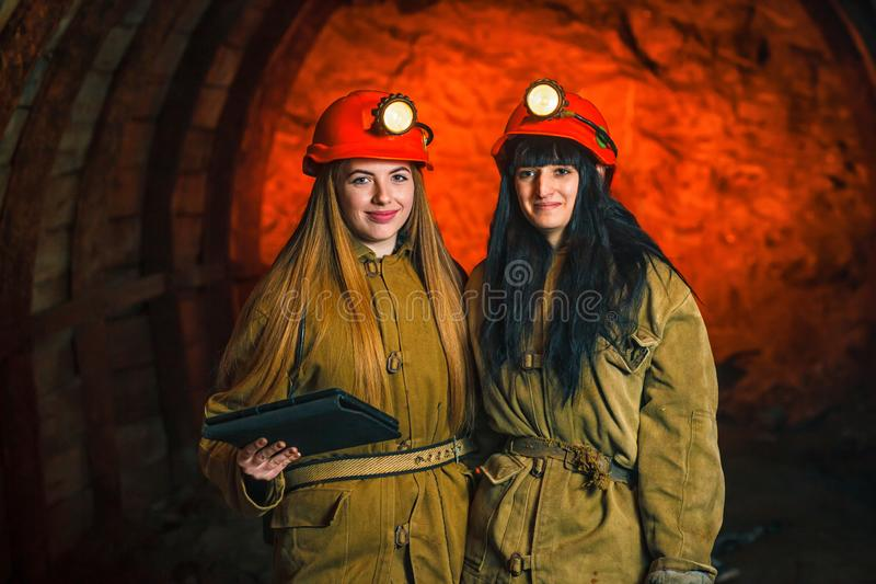 Two miners in the mine. Girls in red helmets and lanterns in a coal mine. Coal mine work plan. Beautiful girls in a coal mine royalty free stock photography