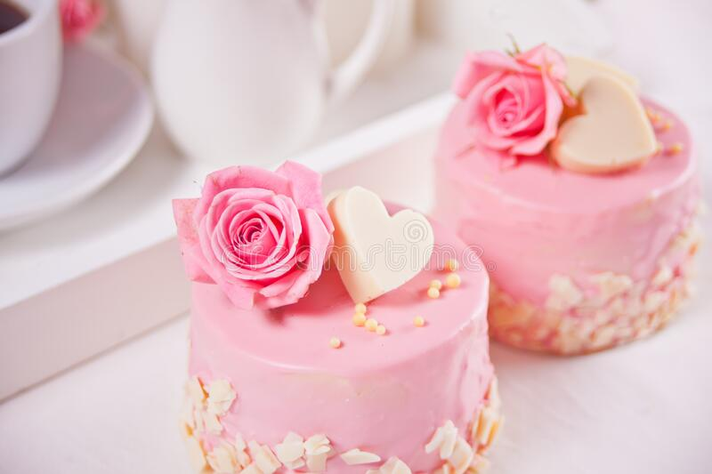 Two mini cakes with roses on a white table. Romantic dinner concept.  royalty free stock image