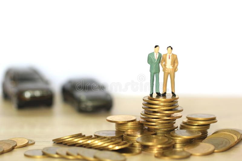 Two miniature businessman standing on stack of coins money on white background, Saving money for car, Finance and car loan, royalty free stock photo