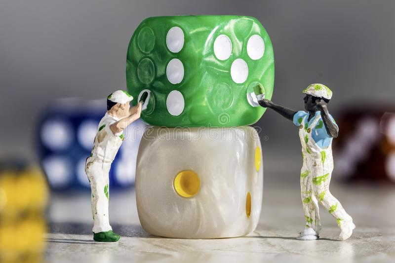 Two Miniature People Painters Painting green Dice with White Pips On a Grey Marble Background stock photography