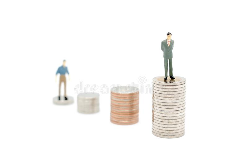 Two miniature people standing on stack of new Thai Baht coins, isolated on white background. Business and finance concept stock images
