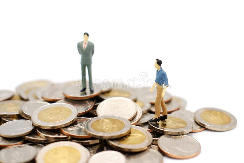 Two miniature people walking and standing on pile of new Thai Baht coins, isolated on white background. Business and finance concept royalty free stock image