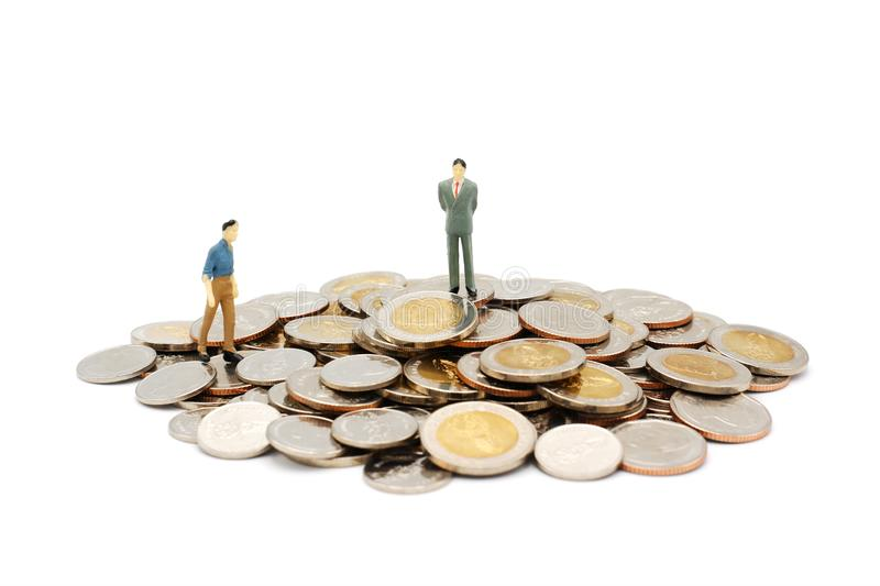 Two miniature people walking and standing on pile of new Thai Baht coins, isolated on white background. Business and finance concept stock image