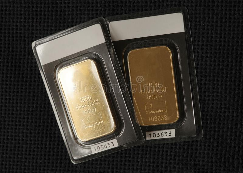 Two minted gold bars weighing 100 grams each against the background of a dark fabric texture.  royalty free stock photography