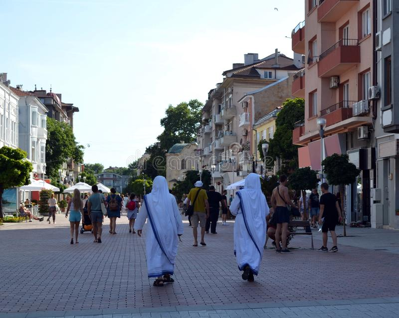Two missionaries of charity walk along a pedestrian street royalty free stock image