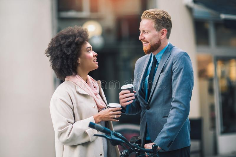 Two mixed race business people talking outside company stock image