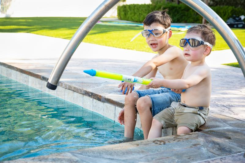 Two Mixed Race Chinese Caucasian Brothers By the Pool in Swimming Goggles stock image