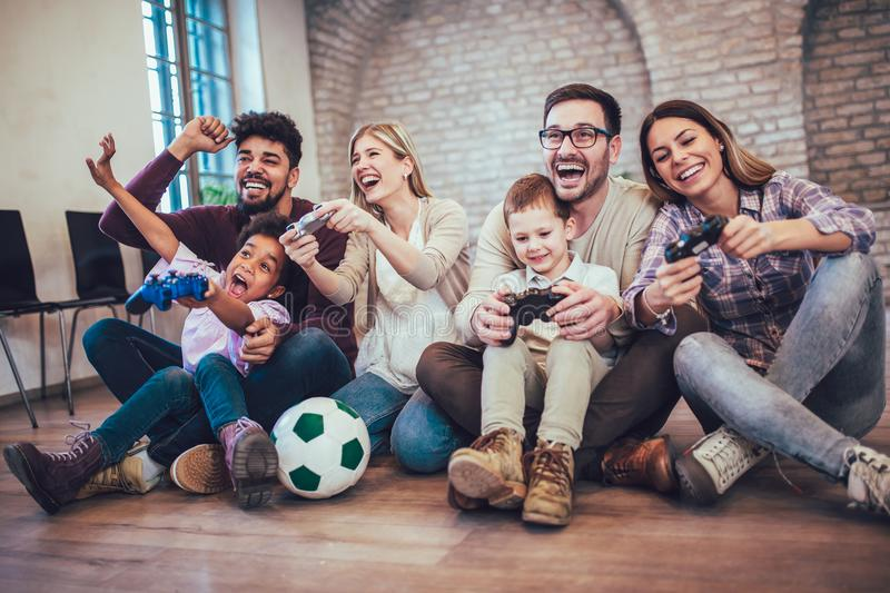 Two mixed race couple play video games with their children. Having fun royalty free stock images