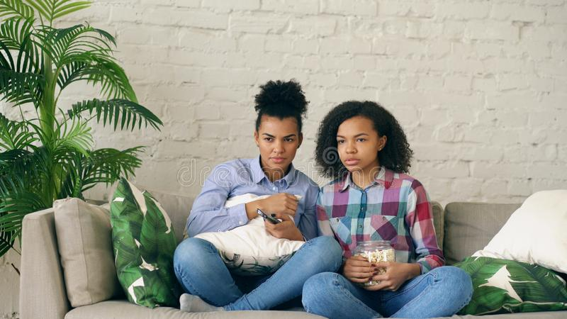 Two mixed race curly girl friends sitting on the couch and watch very scary movie on TV and eat popcorn at home stock images
