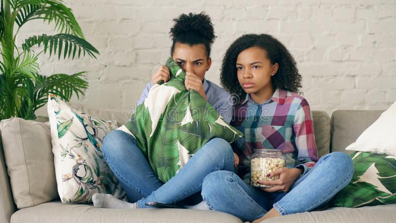 Two mixed race curly girl friends sitting on the couch and watch very scary movie on TV and eat popcorn at home. Two mixed race curly girl friends sitting on the stock photos