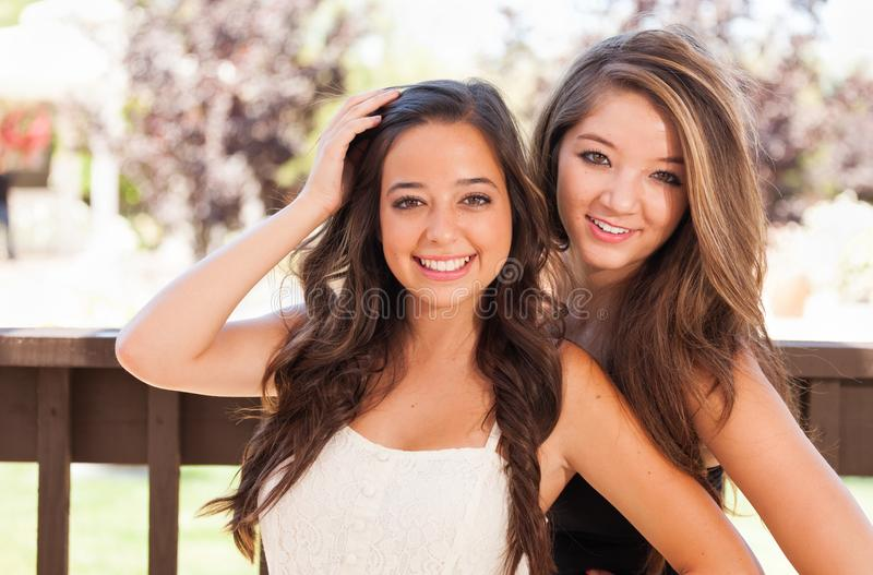 Pretty Mixed Race Teen Girlfriends Pose for Portrait Outdoors. Two Mixed Race Girlfriends Pose for Portrait Outdoors royalty free stock photo