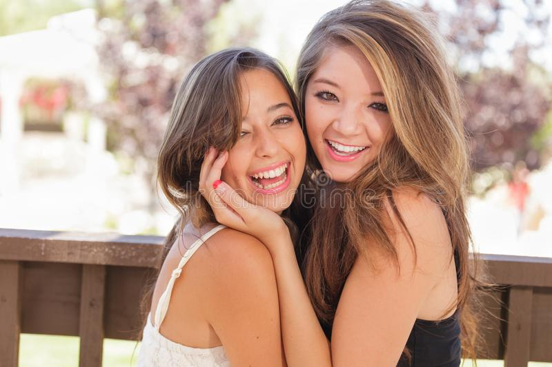 Two Mixed Race Teen Girlfriends Hug for Portrait Outdoors. Two Mixed Race Girlfriends Pose for Portrait Outdoors stock photos