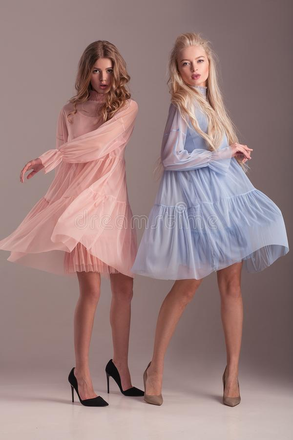 Two models in transparent dresses posing in studio on gray background. royalty free stock image