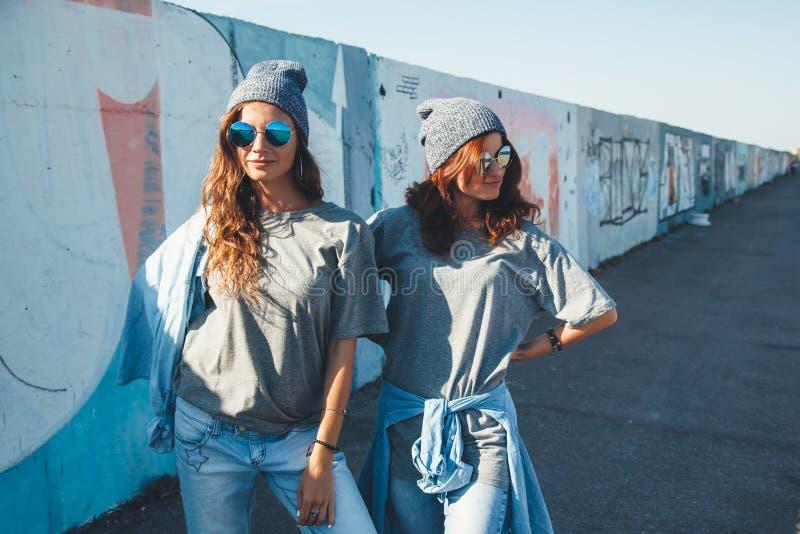 Models wearing plain tshirt and sunglasses posing over street wa stock photos