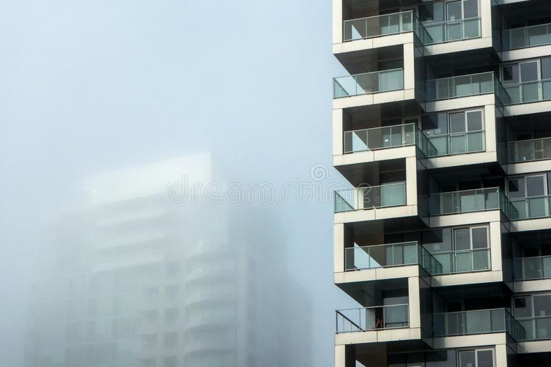 Two modern buildings, with one masked by foggy skies. Two modern buildings provide rhythmic patterns accentuated by one development shrouded by fog royalty free stock image