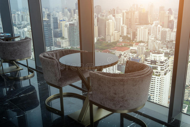 Two Modern Chair and circle glass table on tower office room wit royalty free stock image