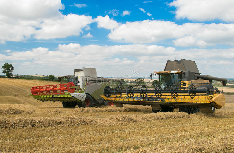 Two modern combine harvester cutting crops. Modern new holland and claas combine harvester cutting crops oilseed working the field corn wheat barley big blue sky royalty free stock photography