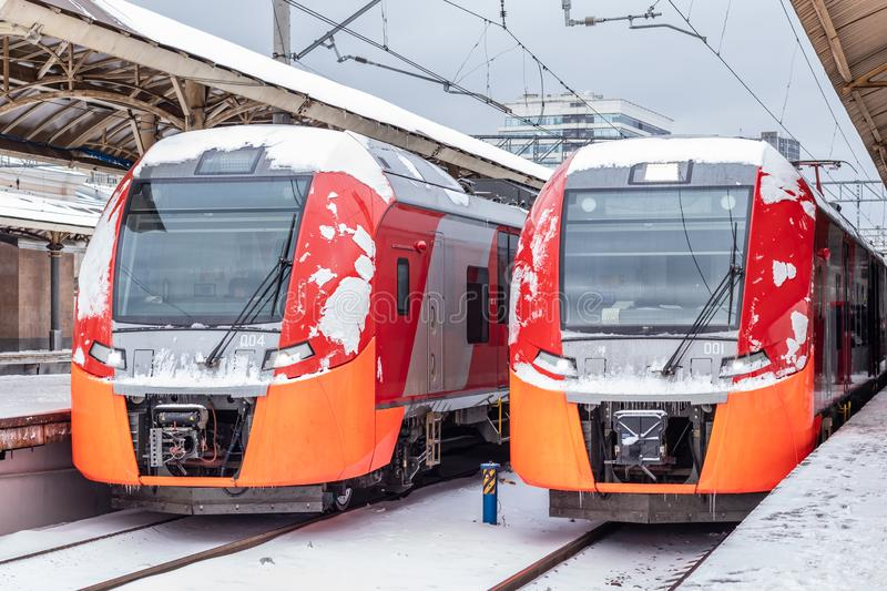 Two modern high-speed red trains on the station platform in winter. Kursky railway station, Moscow, Russia. Two modern high-speed red trains on the station stock photo