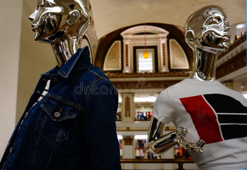 Two modern looking platinum-color mannequins wearing casual clothes for women, with the amazing decor and architecture of Macys royalty free stock photography