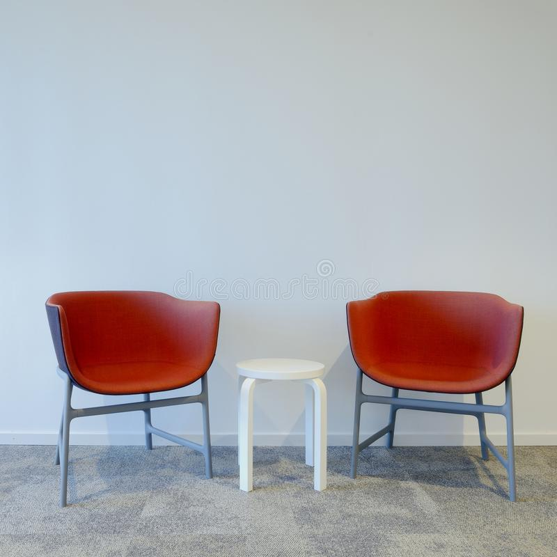 Two Modern red Chairs. And one white footstool stock image