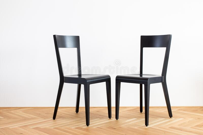 Two modern simplistic black chairs on a wooden flor in front of white background. Modern simplistic black chairs on a wooden flor in front of white background stock photos