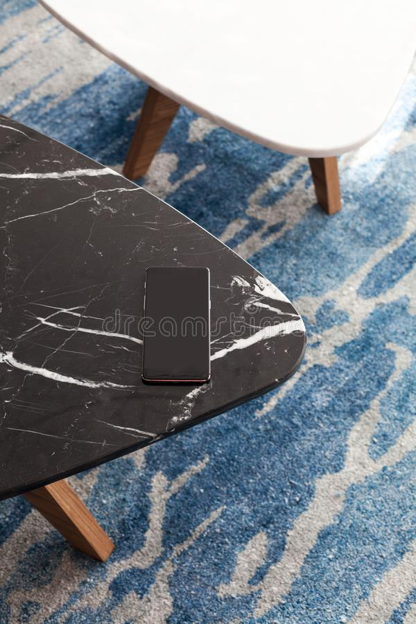 Two modern stool made of black and white artificial stone. Stands on a carpet with fine nap, a top view. The mobile phone lies on a new small chair stock photos