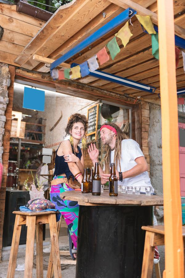 Two modern young hippies sitting in nice alcohol bar stock photography