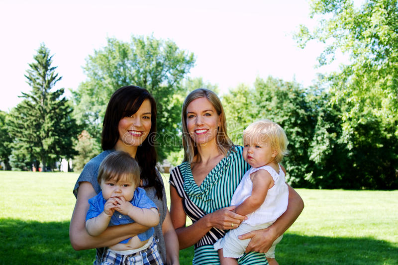 Two Moms with babies on their hip royalty free stock photos