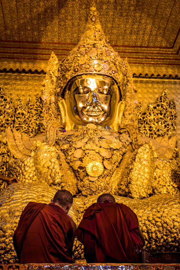 Two monks praying by the golden Buddha statue, Myanmar (Burma). Two monks praying by the golden Buddha statue in a temple in Myanmar (Burma stock photo
