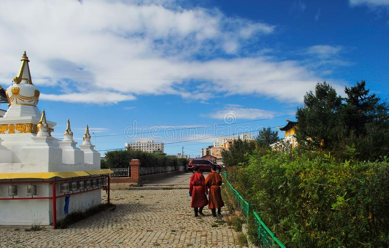 Two monks walk through the territory of a Buddhist monastery. Ulaanbaatar, Mongolia. royalty free stock photography