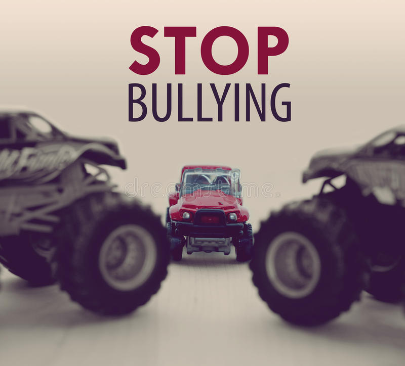 Two Monster Trucks bullying a small car. With Stop Bullying sign royalty free stock photos