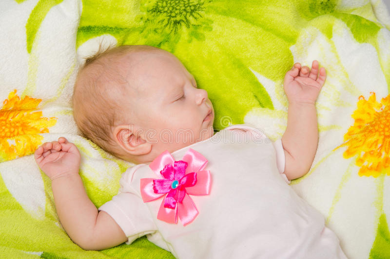 The two-month baby carefree sleeping on the bed. A two-month baby girl Europeans lies on a soft bed on colored coverlet stock images