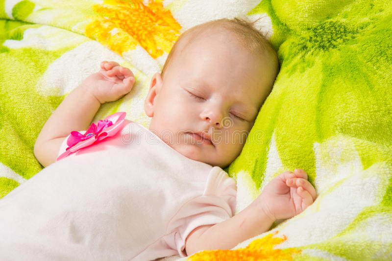 The two-month baby carefree sleeping on a soft bed. A two-month baby girl Europeans lies on a soft bed on colored coverlet royalty free stock image