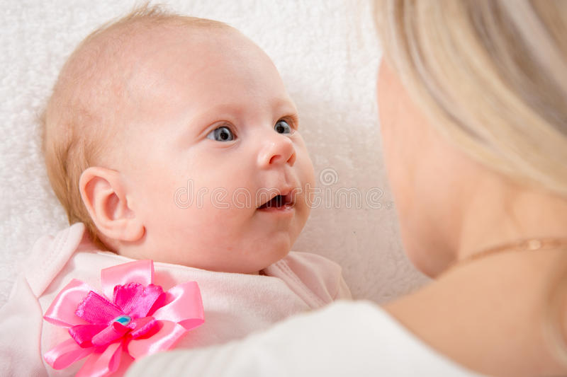 The two-month baby looking at his mother. A two-month baby lying on his back on the bed, sitting next to the child and mother looking at her stock photo